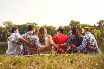 Fototapeta Young people sit on the grass hugging in nature in the park obraz