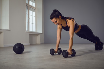Athletic girl in black sportswear doing push-up exercises in a room indoors.