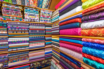 Colored textile or fabric at a street Asian Market, shelves with rolls of fabric and textiles