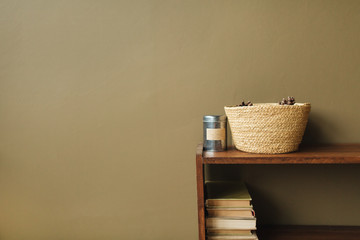 Modern minimal interior design concept. Straw basket, books on wooden stack on olive background.