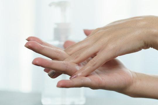 Female hands using wash hand sanitizer gel pump dispenser. Clear sanitizer in pump bottle, for killing germs, bacteria and virus.