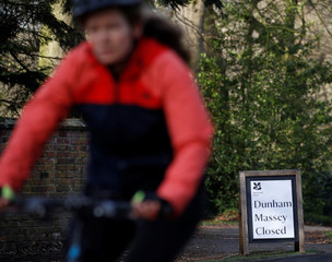A woman cycles past a sign informing that the National Trust property at Dunham Massey is closed in Altrincham