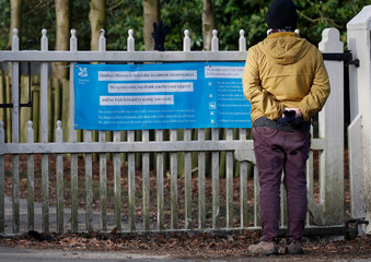 A walker looks at a sign informing that the National Trust property at Dunham Massey is closed, in Altrincham