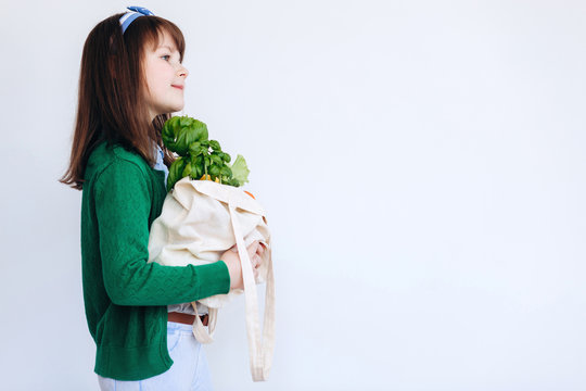 Little girl holding textile grocery bag with vegetables. Zero waste concept. Package-free food shopping. Eco friendly natural bag with organic fruits and vegetables.