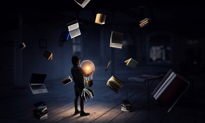 Wall Mural - Boy holding a light bulb with books around him