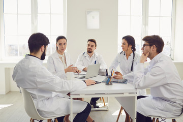 Group of practicing doctors in a meeting discuss the diagnosis of a patient standing in a clinic office.