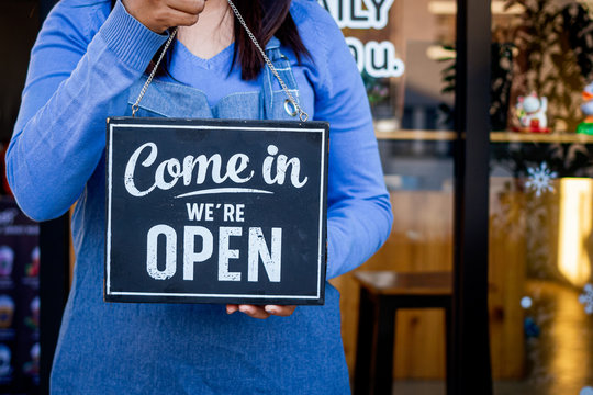 Woman Holding up a shop sign saying:Come in we're open