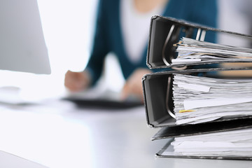 Binders with papers are waiting to be processed by business woman or bookkeeper working at the desk in office back in blur. Audit and tax concept