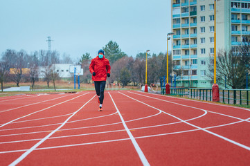 Runner wearing medical mask, Coronavirus pandemic Covid-19 in Europe. Sport, Active life in quarantine surgical sterilizing face mask protection. Outdoor run on athletics track in Corona Outbreak