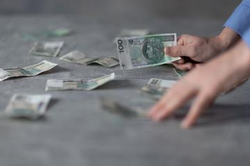 Polka gotówka na stole, ręka trzymająca banknot
