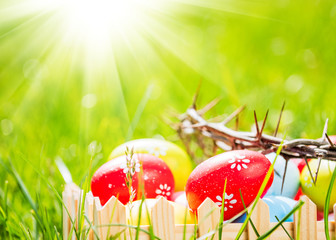 Crown of thorns and colorful eggs in green grass at sunny day. Easter background