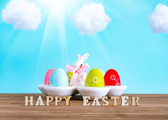 Colorful easter eggs and cute bunny on wood table. Festive decoration