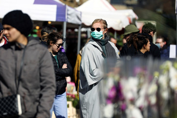 A woman wearing a protective face mask walks through Columbia Road Flower Market, during the coronavirus disease (COVID-19) outbreak, on Mother's Day in London