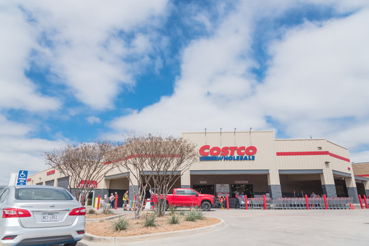 Busy customers walking in and exit the Costco Wholesale store in Lewisville, Texas in cloud blue sky