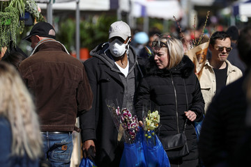 A man wearing a protective face mask walks through Columbia Road Flower Market, during the coronavirus disease (COVID-19) outbreak, on Mother's Day in London