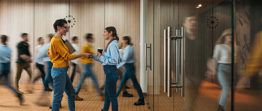 Business people handshaking on background of crowd office employees at coworking center. People at motion blur. Concept of working at action. Group of coworkers at open space. Wide image