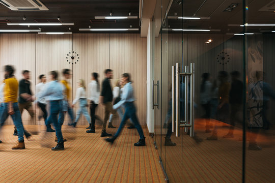 Group of office employees at coworking hall. Business people walking at modern open space. Motion blur. Concept