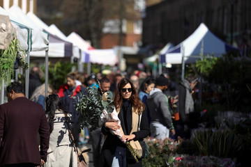A woman carries flowers through Columbia Road Flower Market, during the coronavirus disease (COVID-19) outbreak, on Mother's Day in London