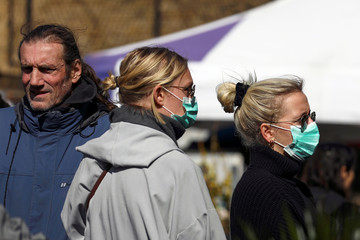 Women wear protective face masks as they walk through Columbia Road Flower Market, during the coronavirus disease (COVID-19) outbreak, on Mother's Day in London