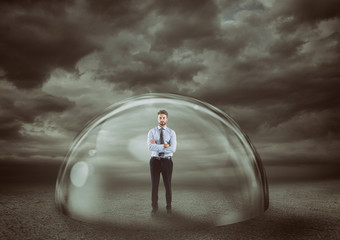 Businessman safely inside a shield dome during a storm that protects him. Protection and safety concept