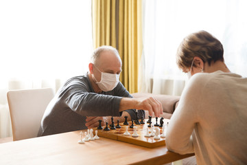 Seniors couple  wearing medical face mask play chess in home. quarantine. health concept. Corona Virus.
