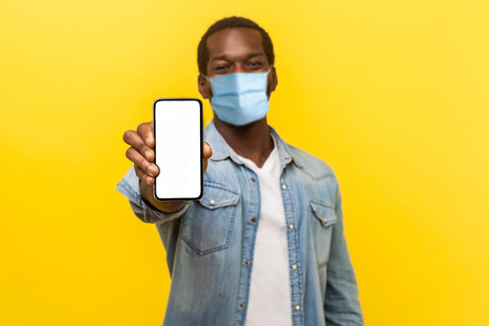 Online service, technology. Portrait of satisfied glad young man with medical mask standing holding out cellphone and smiling broadly at camera. indoor studio shot isolated on yellow background