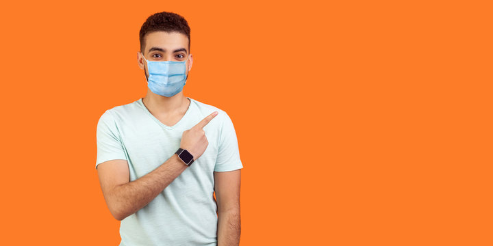 Look here! Portrait of brunette man with medical mask in casual white t-shirt standing pointing at left, empty space for text, advertise. indoor studio shot isolated on orange background