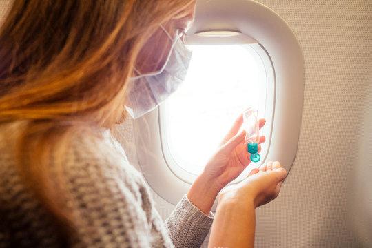 woman applying antibacterial gel while sitting on airplane next to porthole window illuminator before eating a food.coronavirus concept