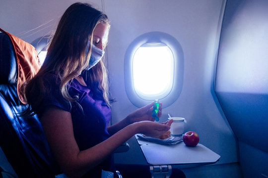 young traveler woman applying applying antibacterial gel while sitting on airplane next to porthole window illuminator before eating a food.coronavirus concept