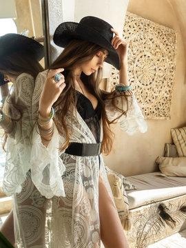 Fashion portrait stylish brunette woman in boho style, a girl in a stylish bohemian chic interior