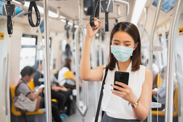 Coronavirus(Covid-19) concept, Asian woman wearing protective face mask to protect infection from coronavirus covid-19 standing at sky train and crowd people