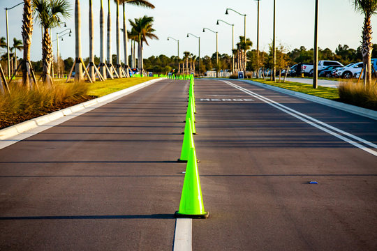 A line of bright green traffic cones separates two empty lanes on a road stretching to the horizon.