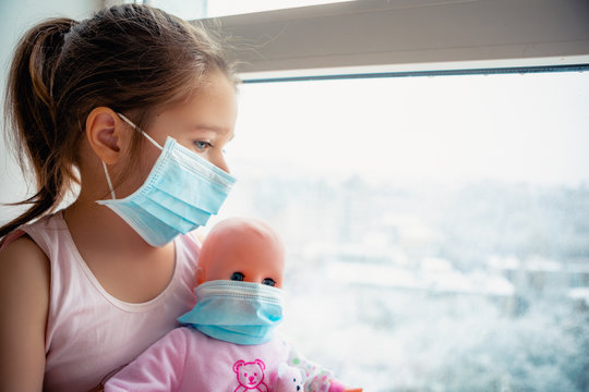 Little girl with doll wearing a protective mask. Copy space. Sadness kid at home in isolation. Sick child Little girls look at the window with longing on the street.