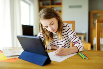 Smart preteen schoolgirl doing her homework with digital tablet at home. Education and distance...