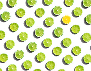 One out unique lemon surrounded by limes - flat lay
