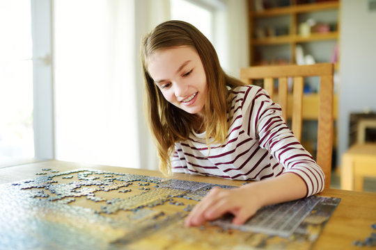 Cute young girl playing puzzles at home. Child connecting jigsaw puzzle pieces in a living room table. Kid assembling a jigsaw puzzle. Fun family leisure.
