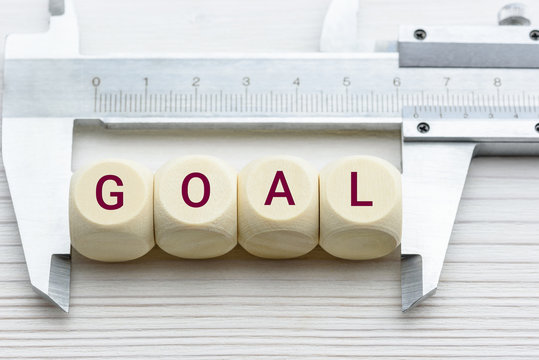 Measuring business goal setting / translate objectives into measurable goals concept : Vernier caliper and wood cubes with a word GOAL, depict tracking on progress or performance of a company targets