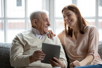 Grown up daughter her old father spend time resting on couch at home. Older man holding tablet...