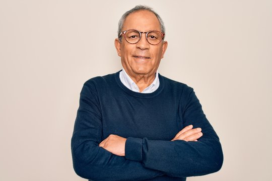 Senior handsome grey-haired man wearing sweater and glasses over isolated white background happy face smiling with crossed arms looking at the camera. Positive person.