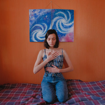 Young woman sitting on bed under galaxy painting and practicing yoga. Home meditation concept