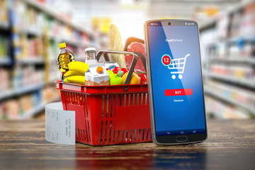 Shopping basket with fresh food and smartphone. Grocery supermarket, food and eats online buying and delivery concept.