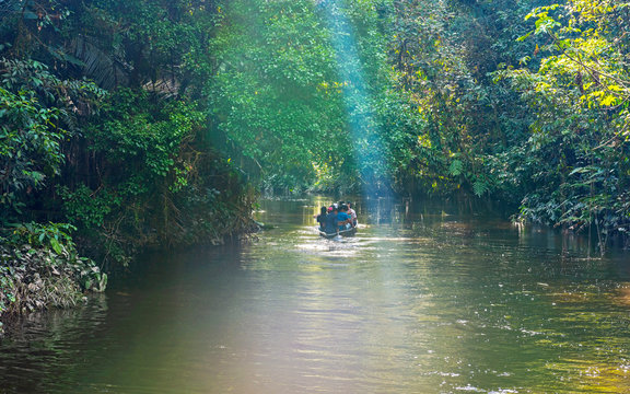 People in a canoe along a canal in the Amazon Rainforest with sunbeam, Yasuni national park, Ecuador.