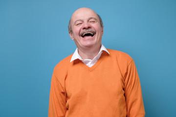 Senior hispanic man in orange sweater laughing on joke. Fotomurales