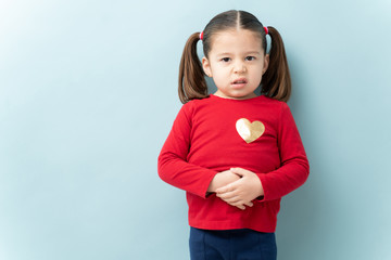 Serious looking little girl touching her belly and feeling sick with a stomachache in a studio Fototapete