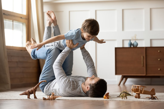 Happy young father lying on floor in living room hold fly with little preschooler son engaged in funny game together, loving dad relax playing with small boy child, enjoy family weekend at home