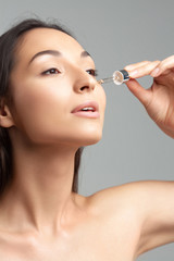 Young beautiful woman with clean perfect skin uses age-sensitive serum in pipette