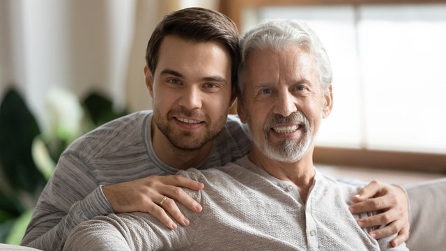 Portrait of smiling elderly father posing looking at camera hugging with adult grown-up son, happy young man embrace mature dad relax together at home on weekend, family value, relationships concept