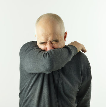 man coughing in an elbow