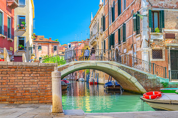 Keuken foto achterwand Venetie Bridge across narrow water canal in Venice with moored boats between old colorful buildings with balconies and brick walls, blue sky, Veneto Region, Northern Italy. Typical Venetian cityscape