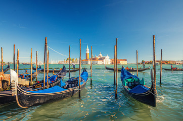 Gondolas moored docked on water in Venice. Gondoliers sailing San Marco basin waterway. San Giorgio Maggiore island with Campanile San Giorgio in Venetian Lagoon, blue clear sky, Veneto Region, Italy